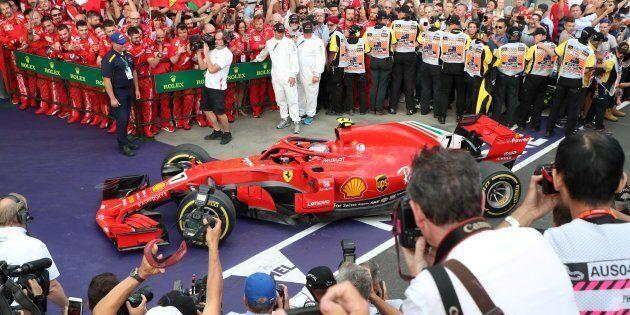The team of Ferrari's German driver Sebastian Vettel waits to congratulate him after he won the Formula...