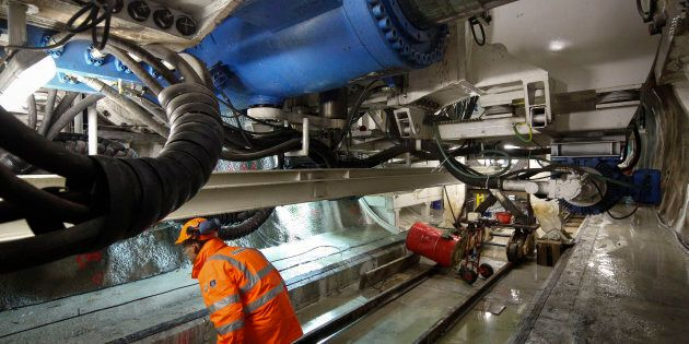 A worker operates on a drill machine in the tunnel of a high-speed train line, known as TAV (Treno Alta...