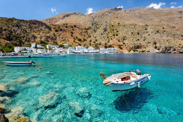 Small motorboat at clear water bay of Loutro town on Crete island,