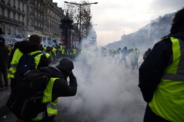 'Yellow vests' (gilets jaunes) demonstrators stand amid tear gas near the Champs Elysees avenue in Paris...