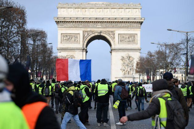 Protestors wearing 'yellow vests' (gilets jaunes) hold French flag near the Arc de Triomphe in Paris...