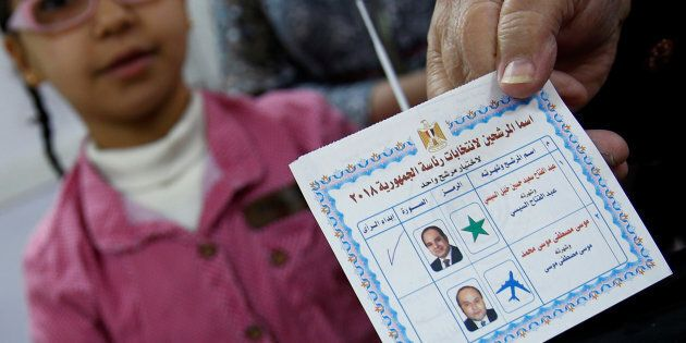 An Egyptian woman shows her ballot paper with sign for Egypt's President Abdel Fattah al-Sisi before...