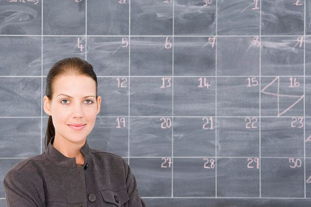 A young woman in front of a blackboard marked out as a