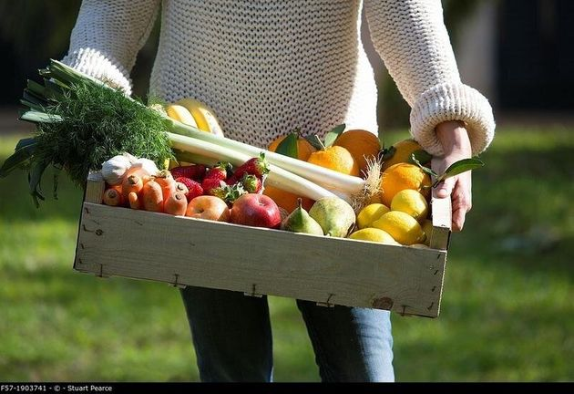 Woman carrying a wooden crate of healthy fruit &