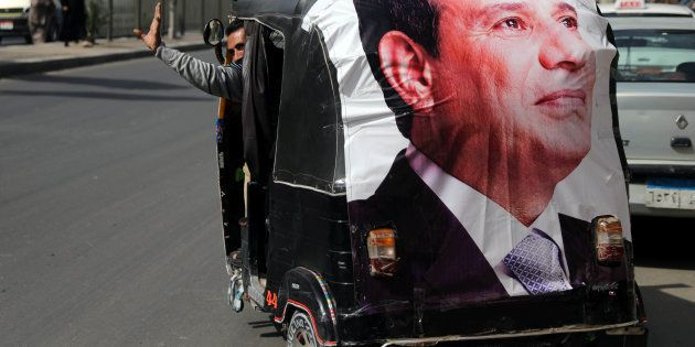 A man gestures as he rides a motorized vehicle showing a poster of Egyptian President Abdel Fattah al-Sisi...
