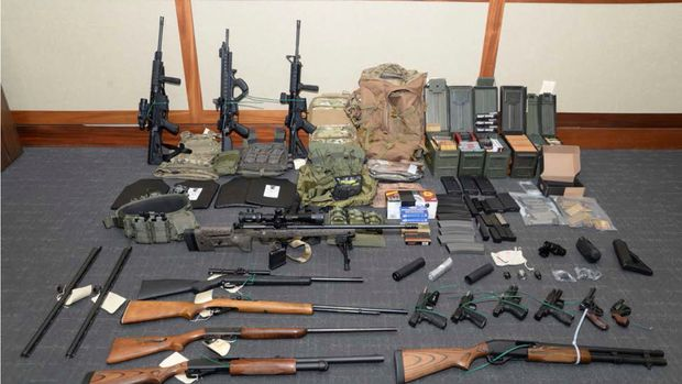 FILE - This file image provided by the U.S. District Court in Maryland shows a photo of firearms and ammunition that was in the motion for detention pending trial in the case against Christopher Paul Hasson. Hasson, a Coast Guard lieutenant accused of stockpiling guns and compiling a hit list of prominent Democrats and network TV journalists looked at other targets: two Supreme Court justices and two executives of social media companies, according to federal prosecutors in a court filing Tuesday, April 22, 2019. (U.S. District Court via AP, File)
