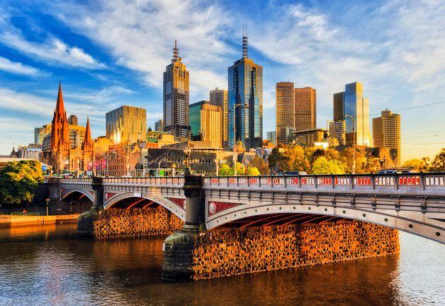 Warm morning light on high-rise towers in Melbourne CBD above Princes bridge across Yarra