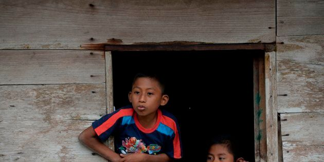 Children look out of a window as the coffin of Guatemalan seven-year-old Jakelin Caal, who died in a...