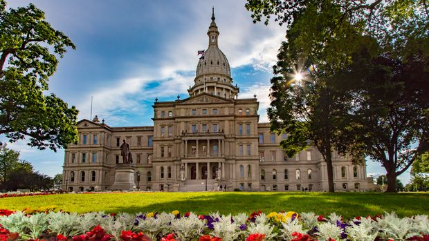 The beautiful capitol building in Lansing, Michigan, framed by lush green trees and lawn, with rows of blooming flowers in the foreground.