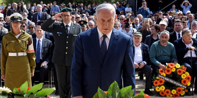 Israeli Prime Minister Benjamin Netanyahu lays a wreath during a ceremony marking the annual Holocaust...
