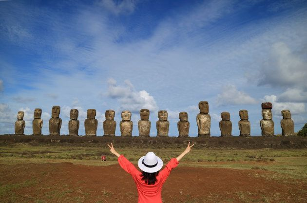 One female raising her arms happily in front of Moai statues of Ahu Tongariki on Easter Island, Chile,...