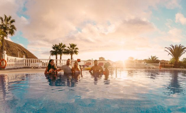 Happy friends drinking champagne in pool party at sunset - Rich people having fun in exclusive tropical...