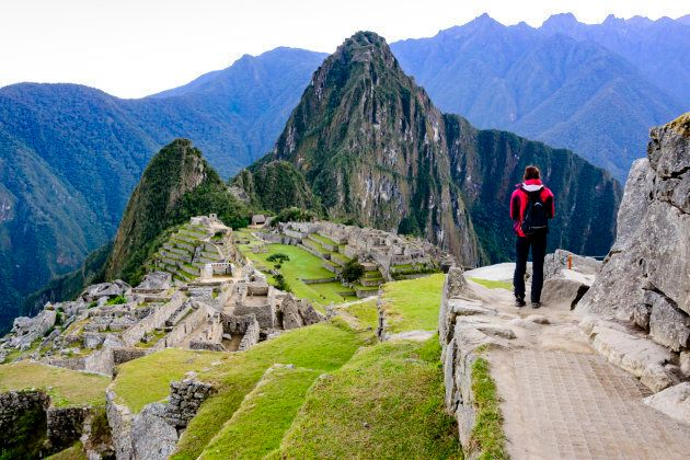 Woman standing on a ledge and overlooking the Inca ruins of the city of Machu Picchu seen in the