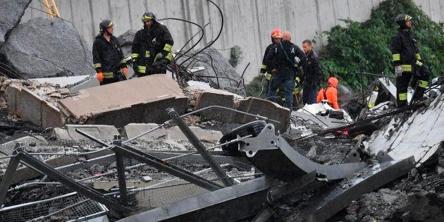 Rescues work among the rubble of the collapsed Morandi highway bridge in Genoa, northern Italy, Tuesday,...