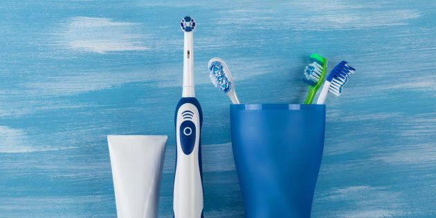 In glass are mechanical toothbrushes, next electric and toothpaste in the bathroom, on blue