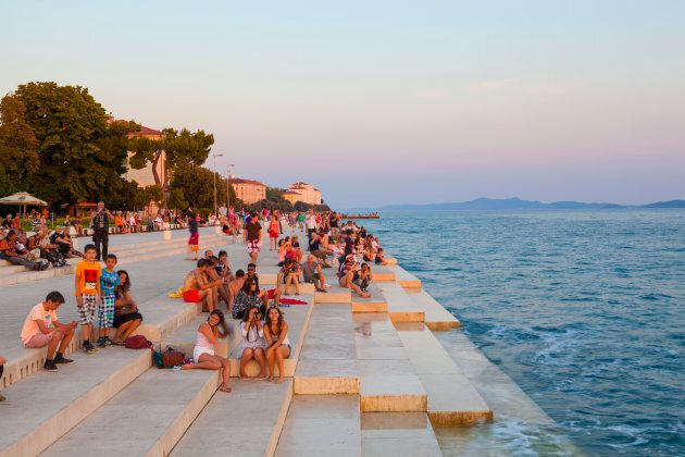 Tourists take in the sunset while listening to The Sea Organ (Morske Orgulje) by Nikola Basic, Zadar,...