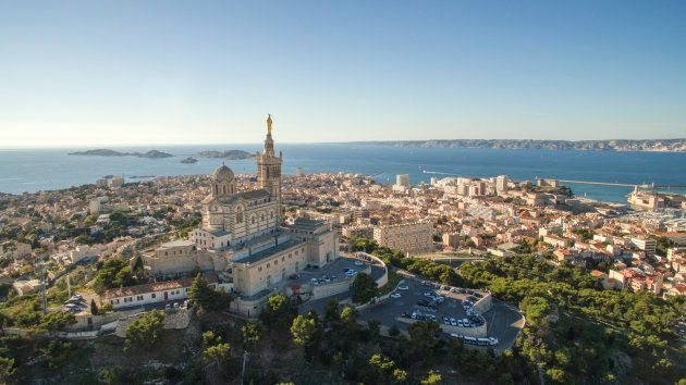 High angle view of cityscape by sea. Notre Dame de la Garde in Marseille against clear sky. Buildings...