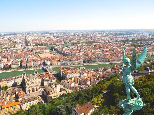 Cityscape with statue of angel, Lyon,