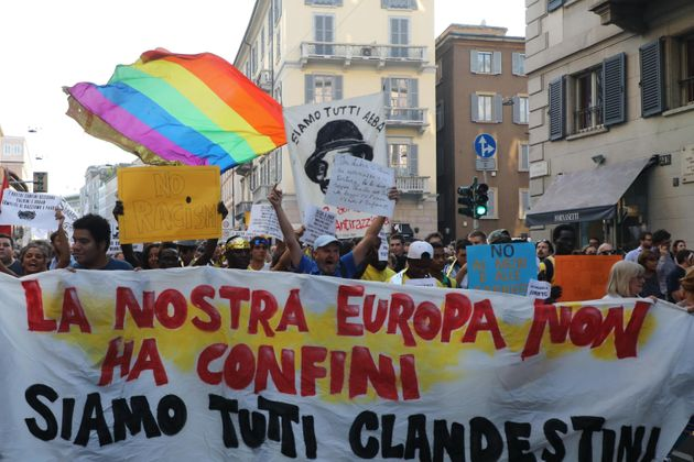 People show banners as they take part in the demonstration 'Europe without walls' organized in San Babila...