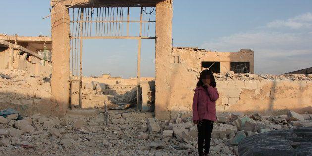 Baraa, 7 anni si trova davanti alla sua scuola in rovine, a