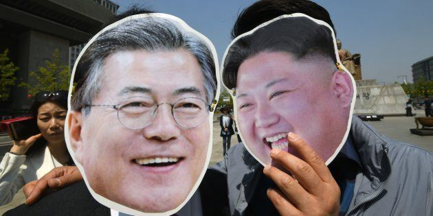 South Korean activists wearing masks of South Korean President Moon Jae-in (L) and North Korean leader...