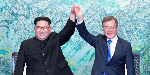 South Korean President Moon Jae-in and North Korean leader Kim Jong Un raise their hands at the truce...