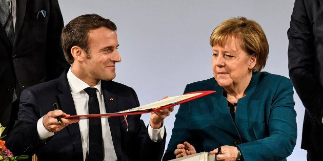 German chancellor Angela Merkel, right, and French President Emmanuel Macron, left, change documents...