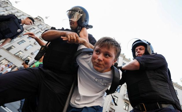 Police officers detain a protester during a rally against planned increases to the nationwide pension...