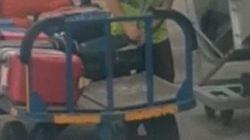 Un passeggero riprende un addetto ai bagagli mentre apre una valigia e