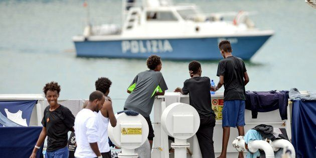 Migrants gather on the deck of the Italian Coast Guard vessel 'Diciotti' in the Sicilian port of Catania,...