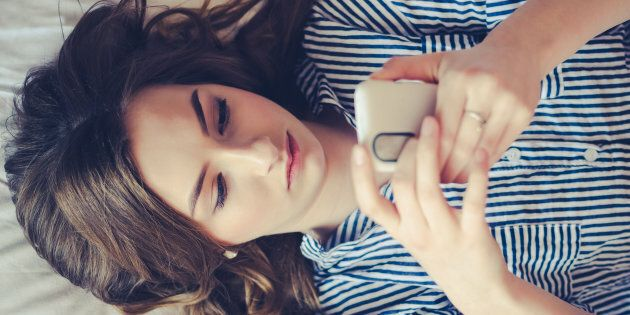 Closeup of sad teenage girl lying in bed using her mobile. Young pretty woman with bored expression looking...