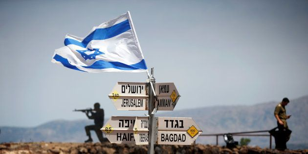 An Israeli soldier stands next to signs pointing out distances to different cities, on Mount Bental,...