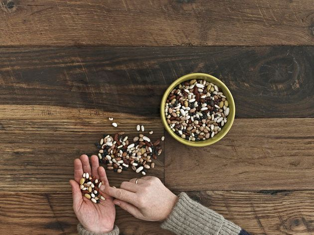 A person sorting different kinds of beans and pulses in her hands on a wooden table