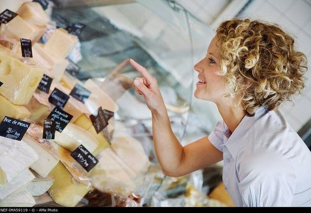 A woman buying cheese
