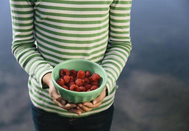 Nine year old girl holding bowl of organic