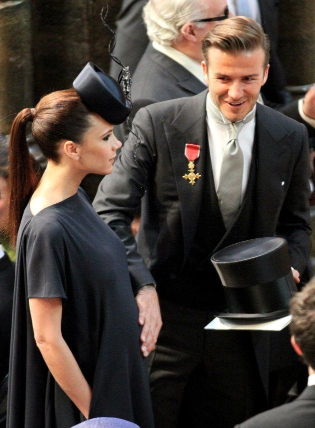Football player David Beckham (R) puts his hand on the stomach of his pregnant wife Victoria as they...