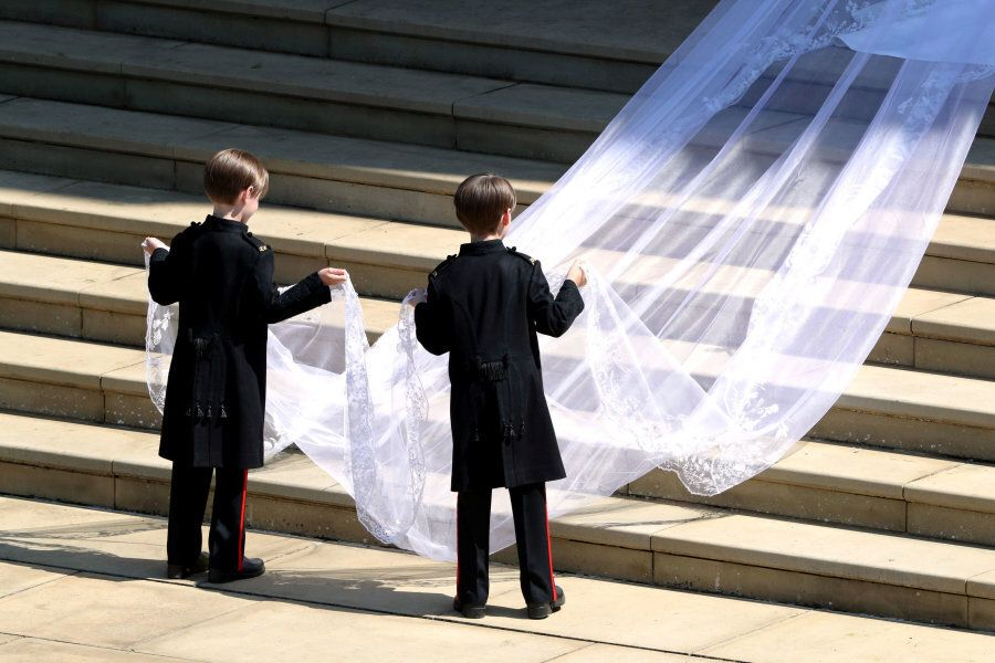Pageboys hold the train of the dress of Meghan Markle as she arrives at St George's Chapel at Windsor...