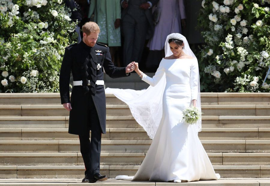 TOPSHOT - Britain's Prince Harry, Duke of Sussex and his wife Meghan, Duchess of Sussex emerge from the...