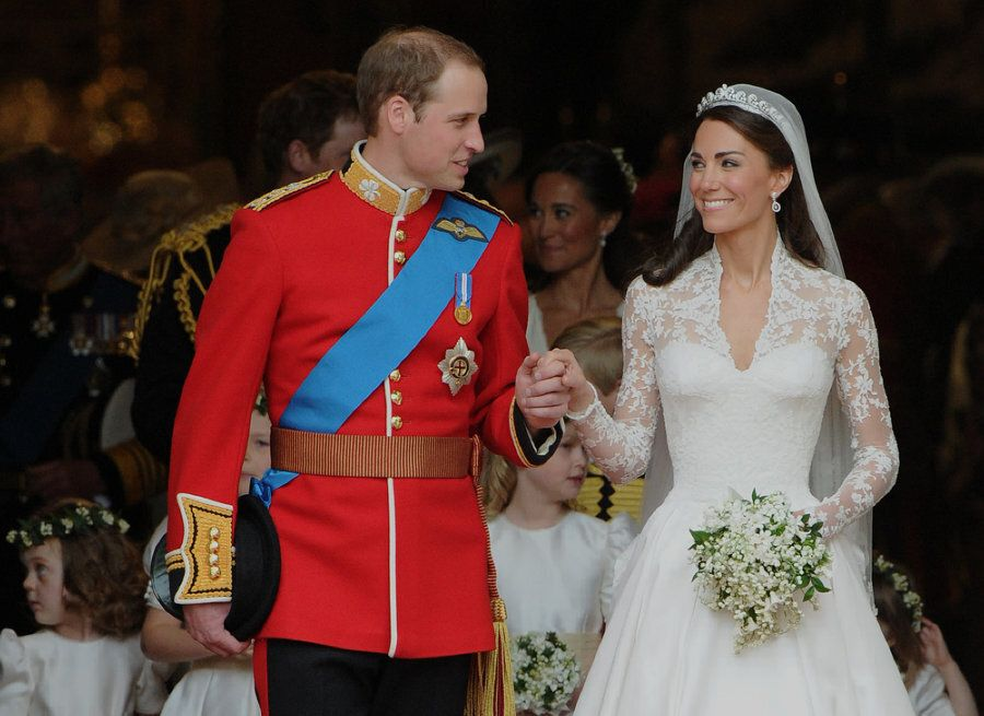 Britain's Prince William and his wife Kate, Duchess of Cambridge, look at each other as they come out...