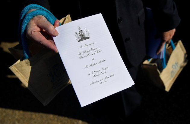 A member of staff holds a service sheet and goodie bags ahead of the wedding of Britain's Prince Harry...