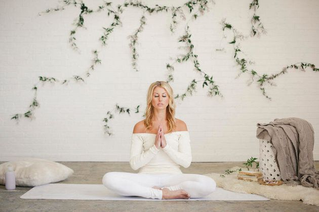 A blonde woman in a white leotard and leggings sitting on a yoga