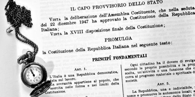testo della costituzione italiana con sopra un vecchio orologio da taschino in bianco e