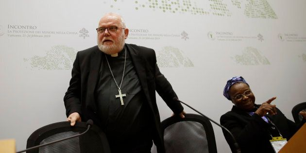 Cardinal Reinhard Marx, left, and Sister Veronica Openibo, leave at the end of a media briefing during...