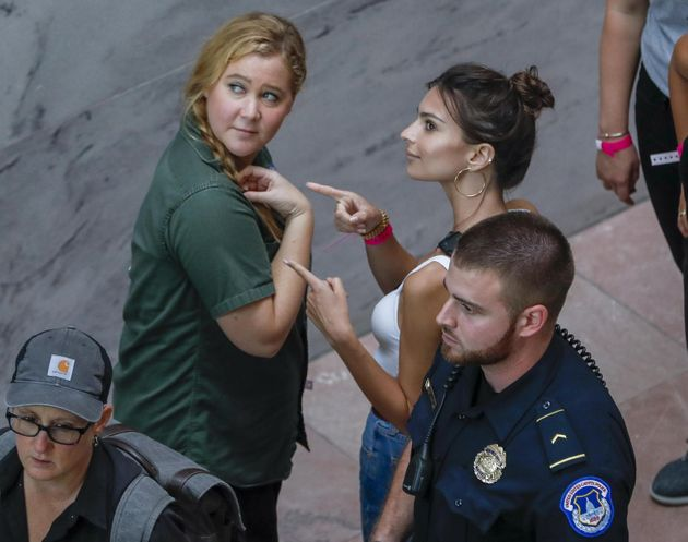 epa07070568 US comedian Amy Schumer (L) and US actress Emily Ratajkowski (R) gesture after getting detained...