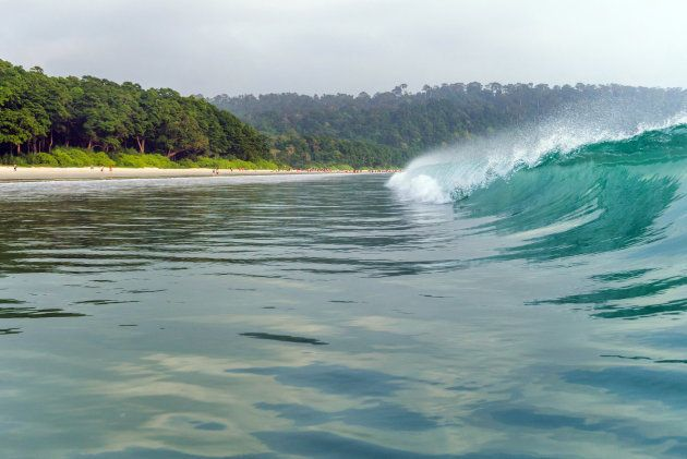 a big wave covers. Radhanagar Beach At Andaman and Nicobar Island, India. view from the sea. bursts of...
