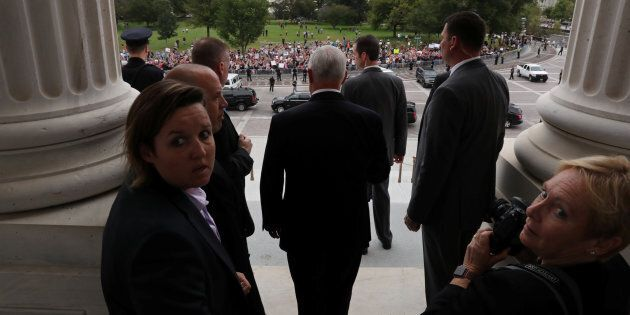 U.S. Vice President Mike Pence faces protestors and the U.S. Supreme Court building in the distance as...