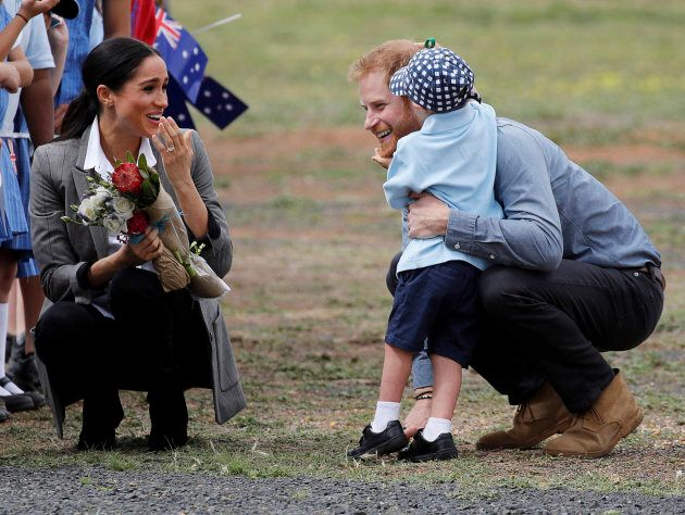 Britain's Prince Harry and Meghan, Duchess of Sussex are embraced by Luke Vincent, 5, on their arrival...