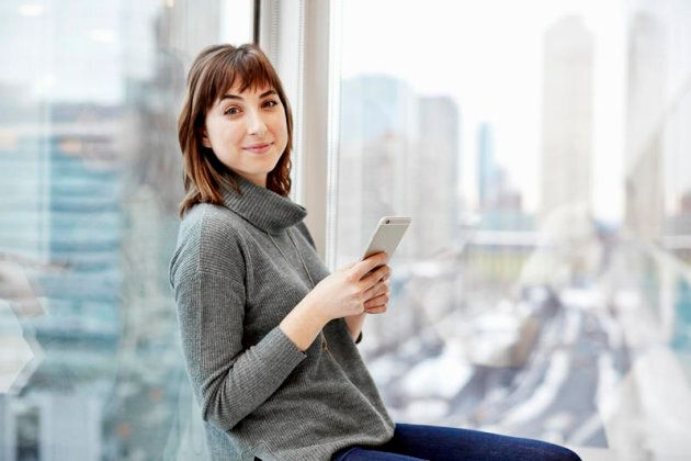 A woman holding a smart phone seated at a window with a city