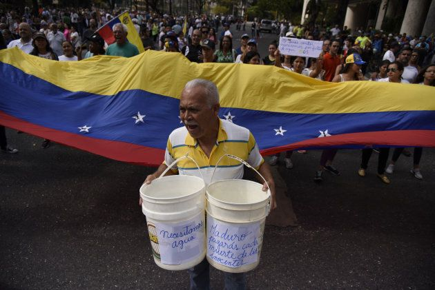 A participant carries buckets during a protest against Venezuelan President Nicolas Maduro in Caracas,...