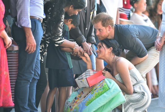 Britain's Prince Harry (C) and and his wife Meghan, the Duchess of Sussex greet well wishers as they...